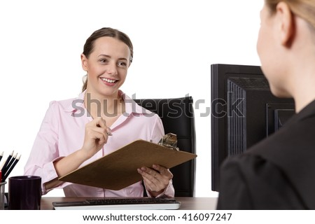 Studio shot of two happy coworkers enjoying a conversation whilst sitting at a desk.  One lady is holding a clipboard.   - stock photo