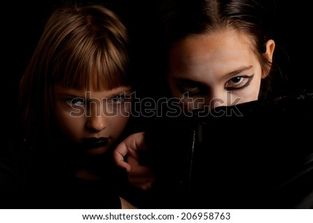 Studio shot of two little girls dressed as vampires looking serious for Halloween - stock photo