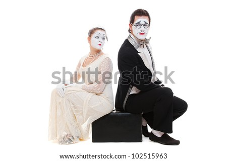 studio shot of two mimes sitting on suitcase. isolated on white - stock photo