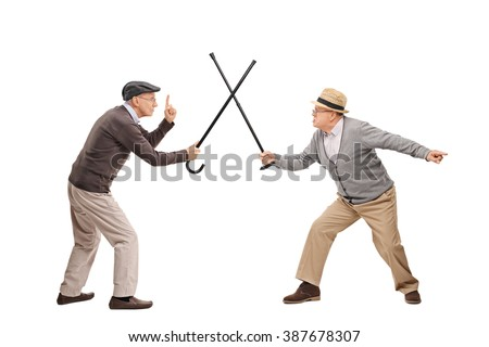 Studio shot of two senior gentlemen having a sword fight with their canes isolated on white background - stock photo