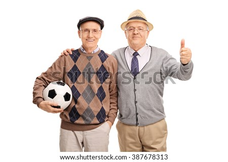 Studio shot of two senior gentlemen holding a football and giving a thumb up isolated on white background - stock photo