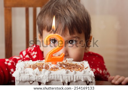 Studio shot of two years old boy with his birthday cake and number two candle. Effect used to create vintage look. - stock photo