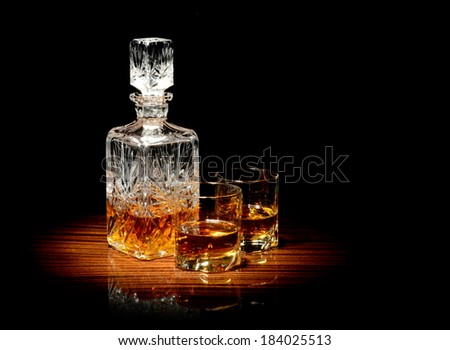 Studio shot of whiskey in a carafe and two glasses isolated on black - stock photo