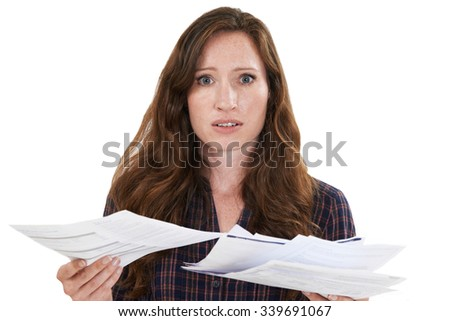 Studio Shot Of Worried Woman Looking At Bills - stock photo