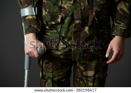 Studio Shot Of Wounded Soldier Using Crutch - stock photo