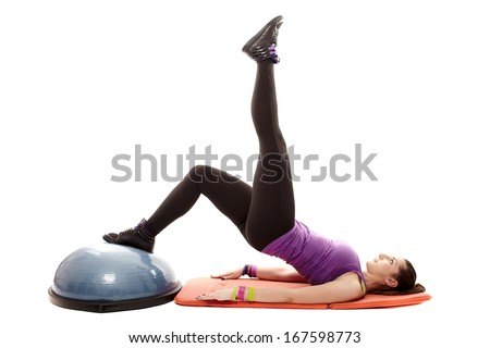 Studio shot of young athletic woman lying on the floor working out her legs and bottom on a bosu ball, isolated over white background - stock photo