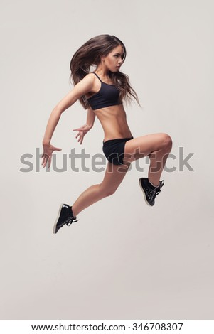 studio shot of young beautiful woman doing gymnastick jump over light grey background - stock photo