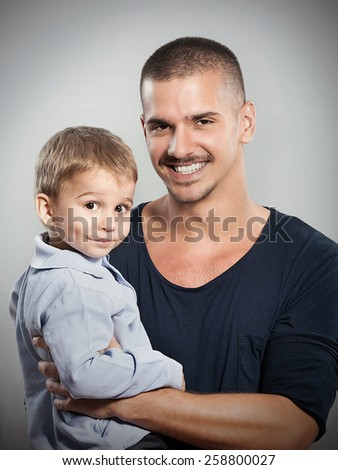 Studio shot of young father carrying his cute little son - stock photo