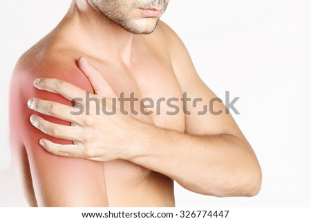 Studio shot of young man with shoulder pain - stock photo