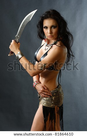 studio shot of young warrior woman holding sword in her hand - stock photo