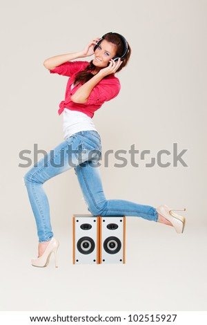 studio shot of young woman in headphones over grey background - stock photo