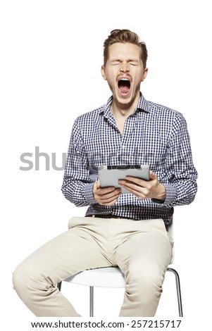 Studio shot of young yawning man. Facial expression. - stock photo