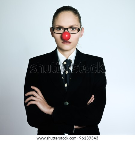 studio shot portrait of a beautiful one young business woman in a costume suit with a clown nose on isolated grey background - stock photo