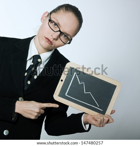 studio shot portrait of one serious business woman holding graphic board with deacreasing curve - stock photo