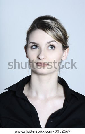 studio shot portraits of a young and cute and expressive woman on a blue grey background - stock photo