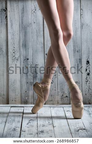 Studio shot, young legs graceful ballerina. Dancer standing on his toes. Close-up. - stock photo
