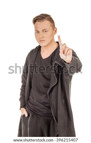 Studio shot young man in black clothes showing one finger. emotions, facial expressions, feelings, body language, signs. image on a white studio background. - stock photo