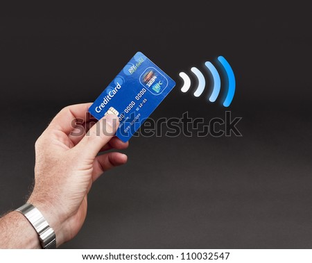 Studioshot of payment action with credit card - contactless payments - stock photo
