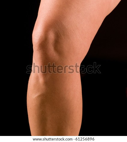 Study of athletic woman's knee, isolated on black - stock photo