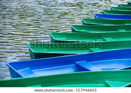 Study Of Solitude. Visions of civilization. Closeup view of a row of leisure rowboats, tied to a dock because of early morning. No one in sight, calm and peaceful time of the daybreak. - stock photo
