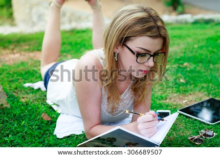 Studying Beautiful Woman Lying Down At The Park Writing On Notebook - stock photo
