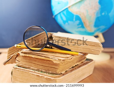 Studying geography composition of a stack of old books, pencil and magnifying glass against the background of the globe and blackboard - stock photo