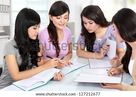 Studying happy young woman reading her book for school together with friends - stock photo