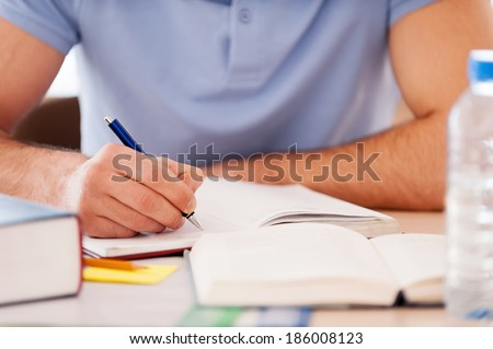 Studying hard. Cropped image of student writing something in note pad while sitting at the desk  - stock photo