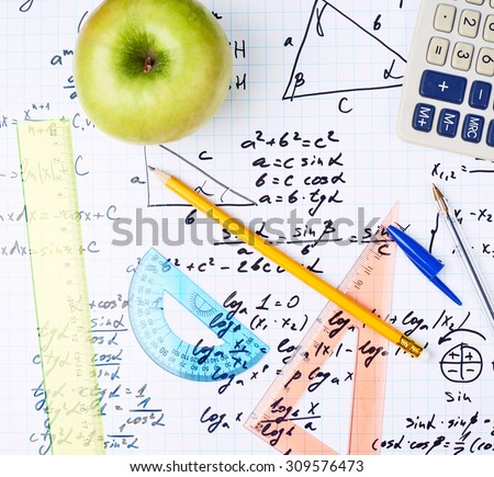 Studying math back to school composition of the green apple and some stationery office supplies lying over the sheet filled with trigonometry equations and formulas - stock photo