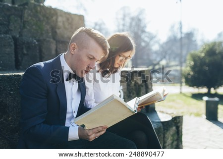 Studying together. Cheerful young nerd couple in glasses preparing to exams while sitting together - stock photo