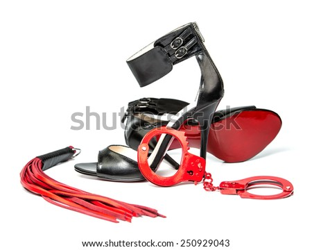 Stuff for sexual role playing: black high heels together with a whip made of red leather and red hand cuffs. - stock photo