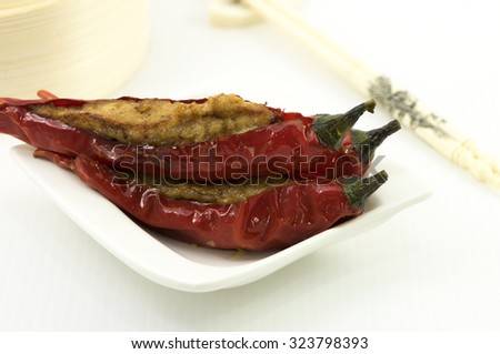 Stuff red chillis with minced meat mix with fish paste. A dim sum style Chinese cuisine prepared as small bite-size portion of food traditionally served in small steamer basket or on small plate. - stock photo