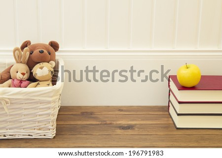 Stuffed animal toys in a basket on the floor. A stack of books and an apple in front of a white wainscot. - stock photo