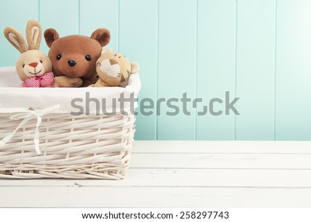 Stuffed animal toys in a basket on the floor. A turquoise wainscot. - stock photo