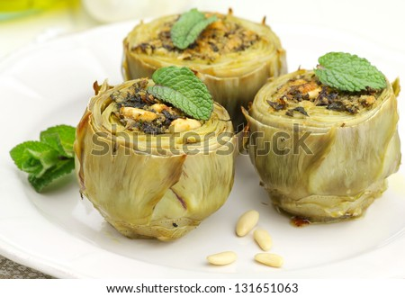 Stuffed artichokes on a plate with fresh mint and pine nuts - stock photo