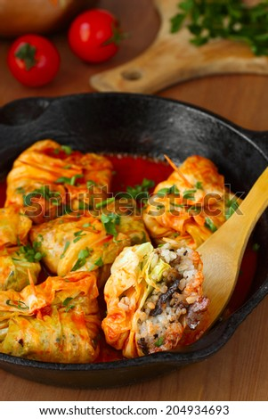 Stuffed cabbage rolls with rice and mushrooms in tomato sauce. Dolma, sarma, or golubtsy - traditional dish of many countries - stock photo