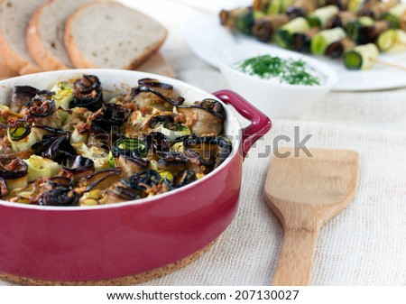 stuffed eggplant and zucchini rolls in red casserole on sackcloth napkin with wooden spoon - stock photo
