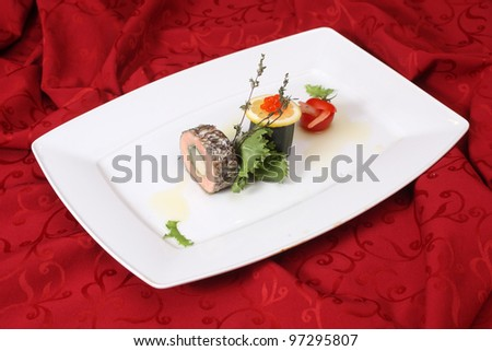 Stuffed fish with vegetables on white plate - stock photo