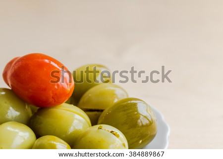 Stuffed green tomatoes with red tomato on wooden background. - stock photo