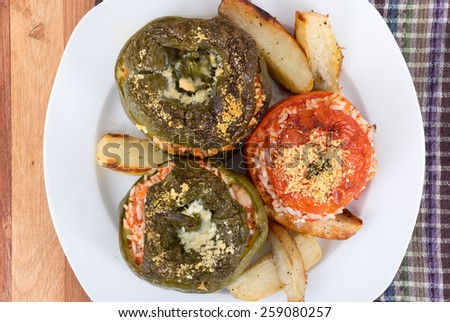 Stuffed pepper and tomato with rice and parmesan cheese - stock photo