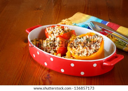 stuffed peppers served in red plate on wooden table - stock photo