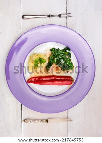 stuffed Red peppers with mashed potatoes and spinach in purple plate , fork and knife on white wooden table, top view - stock photo