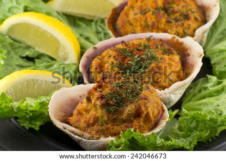 Stuffed seasoned clams garnished with romaine lettuce and lemon wedges on a rustic platter - stock photo
