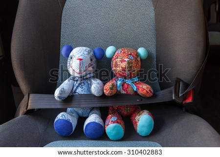 Stuffed toys buckled with safety belt in a car - stock photo