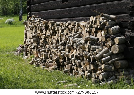 stump stack, pine wood trunks on the wooden wall and green grass background - stock photo