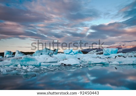 Stunning atmosphere of huge iceberg reflecting in the cool glacial water. - stock photo