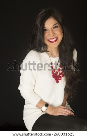 Stunning beauty female model wearing white blouse with a red necklace sitting black background - stock photo