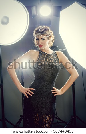 Stunning beauty model posing at studio in light flashes. Professional fashion model. Celebrity. - stock photo