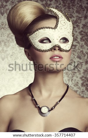 Stunning blonde lady with elegant hair-style and romantic eyes posing with decorated mask on her visage and stylish necklace.  - stock photo