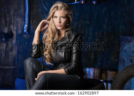 Stunning blonde woman in black leather jacket in the old garage. - stock photo
